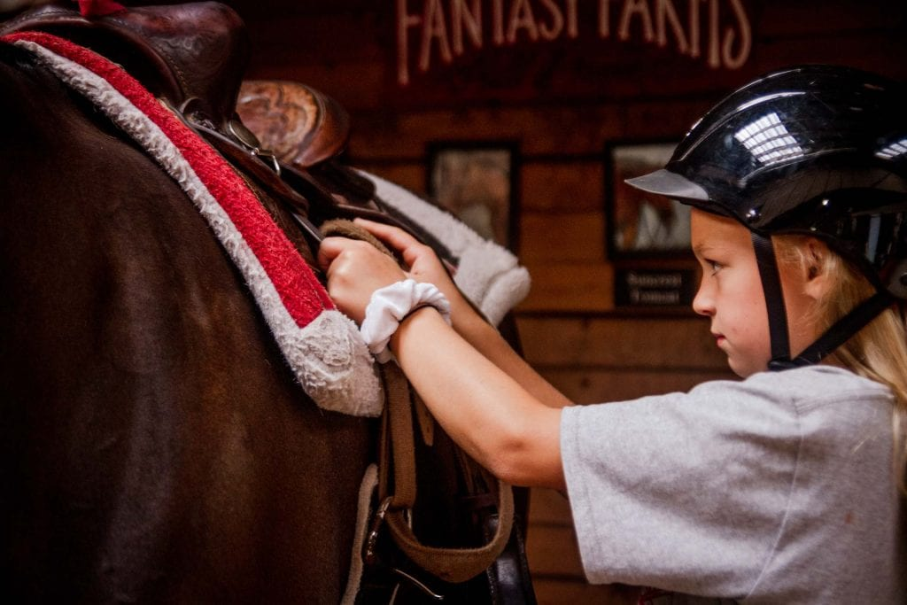girl tacking horse at Fantasy Farms in Turner Oregon with helmet on and saddle